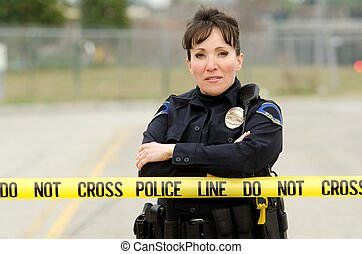 crime scene - a Hispanic police officer standing behind...