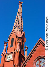 A historic clock tower of Calvary Baptist Church, Washington DC. The church tower lit by evening sun.