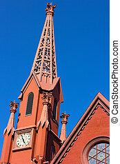 A historic clock tower of Calvary Baptist Church, Washington DC. The church tower lit by evening sun.