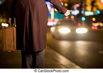 A hitchhiker with an old suitcase is waiting on a sidewalk as night city traffic flows by