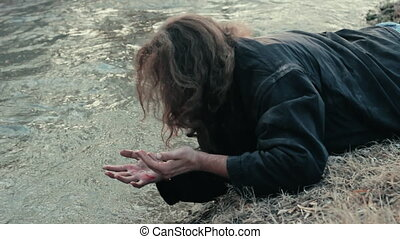 A homeless beggar lies near the river and washes his hands...