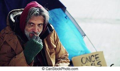 A homeless beggar man sitting outdoors, eating tangerine....