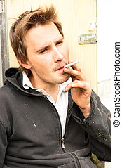 a homeless poor young guy smoking