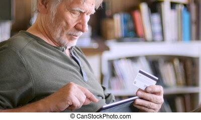 a, homme aîné, commander ligne, à, sien, carte de débit, sur, sien, tablette numérique