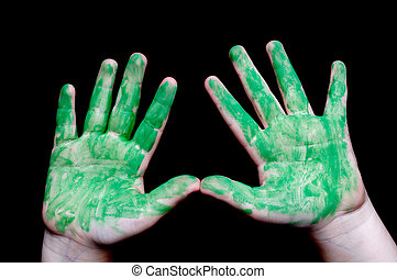 A horizontal image of a child's hands covered in green paint on black