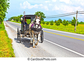 A horse pulling a cart across the streets in regular traffic