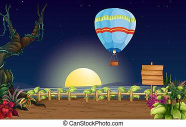A hot air balloon in a bright full moon