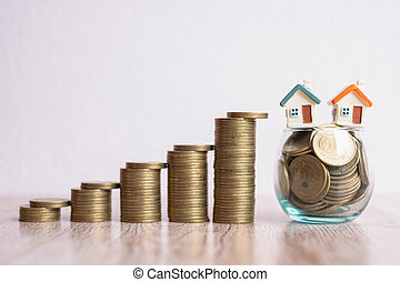A house in a glass jar with coins. Adjoining coin ladder On the top that the coin is about to fall. Risk concept for investing in real estate business, saving money.