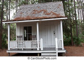 A small house in the woods with chairs on he veranda