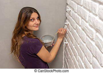 A house painter paints a gray corner of the wall with a small tassel