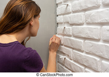 A house painter tends to paint a gray corner of the wall with a small tassel