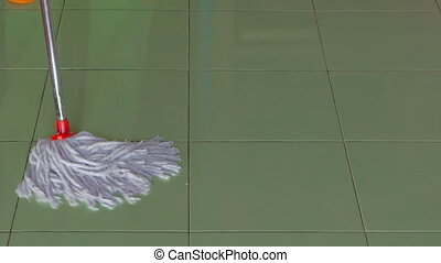 A housewife mops a green floor at her home.