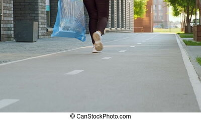 A housewife walks down the street with a bag of household garbage. The camera takes off her legs and follows her