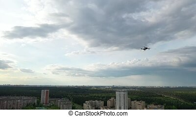 A hovering drone takes off against a cloudy sky and forest ...