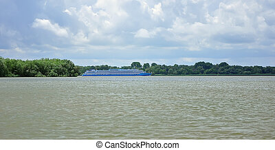 A huge boat goes on the wide river Danube against the blue sky