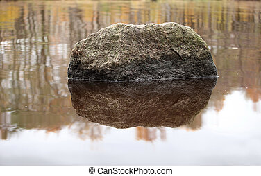 a huge boulder reflected in the water