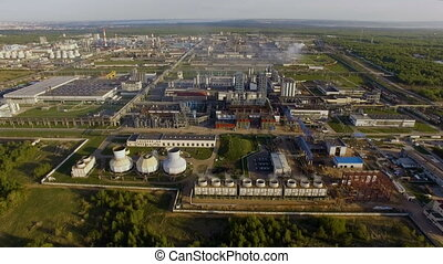 A huge oil refinery with pipes and distillation of the complex on a green field surrounded by forest. Aerial view
