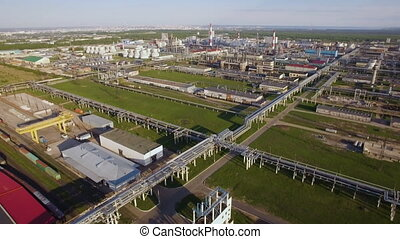 A huge oil refinery with pipes and distillation of the complex on a green field. Aerial view