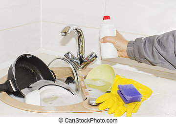 a huge pile of dirty dishes and cleaning supplies in hand
