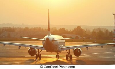 A huge plane is moving on the airport runway on a background of orange sunset