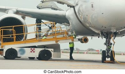 A huge plane standing on the airplane field. Workers helping the plane to take off