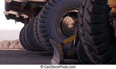 A huge wheel standing trucks. Dump truck. Parking huge heavy trucks. Mining truck. Dump trucks are out of work.