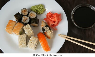 A huge white dish with a variety of sushi rolls from the national Japanese cuisine