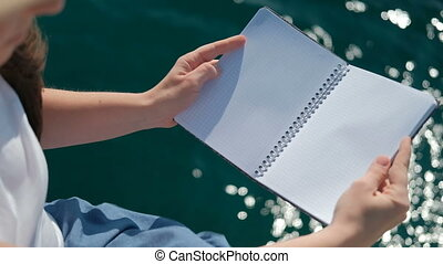 A human being with a hat opens and closes the notebook clean...