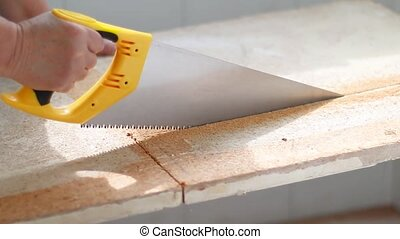 A human hand with a handsaw saws a chipboard in a house.