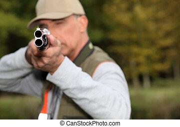 A hunter aiming his rifle