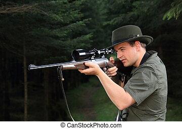 Hunter shooting with his rifle