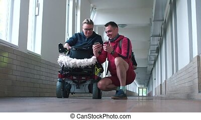 A husband shows his disabled wife good news on a smartphone screen.