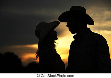 in love young couple on haystacks in cowboy hats - a in love...