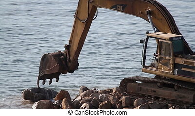 a jcb moving rocks on a beach in mexico