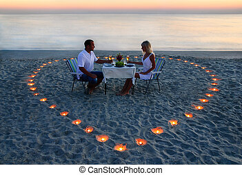a, jeune, amants, couple, part, a, dîner romantique, à, bougies, coeur, sur, les, mer, plage sable