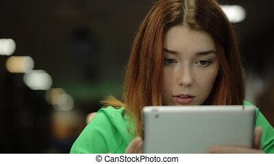 a, jeune femme, tient, a, doigt, les, écran tactile, pc tablette, dévisage, les, écran, et, cherche