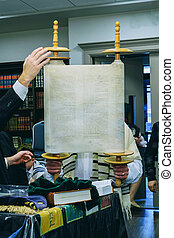 A Jewish man lifts a Torah scroll as he takes part in a Shacharit prayer A group of ultra-Orthodox pray the morning prayer