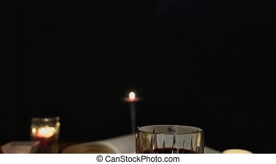 A jib down shot of a candle lit communion setting with wine, bread and the Bible.