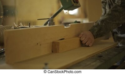 A joiner at the sawmill processes the board on a special ...