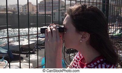 journalist watching binoculars through the fence - a...