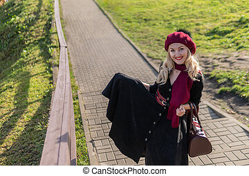 A joyful girl walks up the stairs in burgundy palette and biret, looks at the camera in black clothes, in the fall against the background of a pond there are blue clouds.
