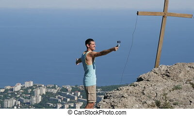 A joyful man in a victorious pose stands at the peak of the mountain shooting himself to the action camera