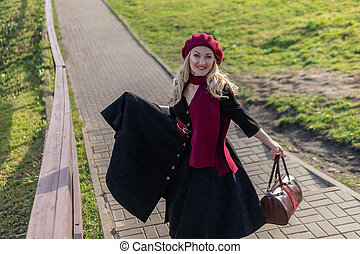 A joyful woman walks up the stairs in burgundy palla and biret, with beautiful eyes in black clothes, in the fall against the background of a pond there are blue clouds.
