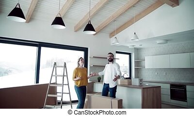 A joyful young couple moving in new home, expressing...