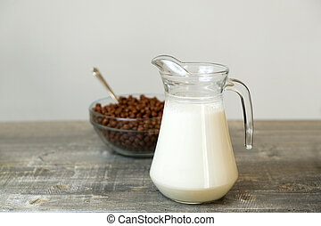 a jug of milk and a bowl of chocolate cereal in the background