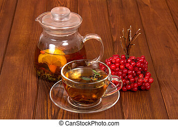 A jug with hot tea and viburnum from colds, on table