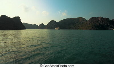 A junk boat anchored in beautiful Ha Long Bay, Vietnam at sunset