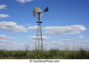 A Kansas Country Windmill in a pasture with blue sky, whiteclouds, and greengrass, and fence.