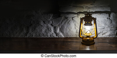 A kerosene lamp on an old wooden background