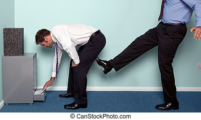 A kick up the backside - Photo of a businessman bending over...